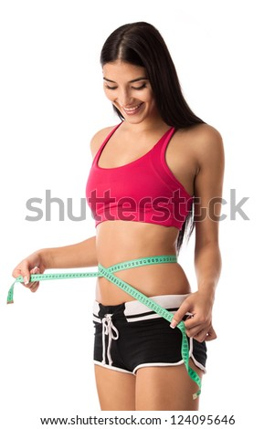 Beautiful young girl checking her waistline with a measuring tape