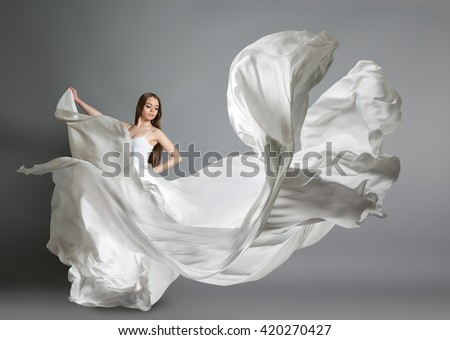 beautiful young girl dancing. The girl in flying white dress. A white cloth is flying in the air. White light dress