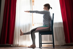 Beautiful young girl doing exercises at home sitting on chair