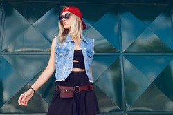 Beautiful young girl dressed in a stylish street style outfit posing in front of a green tin background. Dressed in black with a denim vest, red baseball cap, sunglasses and with choker around neck.