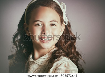 Beautiful young girl dressed in white. First Communion. Perfect teeth and smile, long curly hair. Dark background, close up studio shoot. Vintage picture.