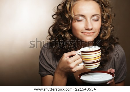 Beautiful young girl drinking tea or coffee