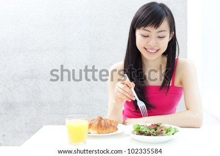 beautiful young girl eating breakfast