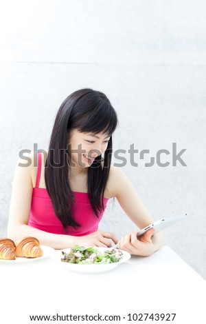 beautiful young girl eating breakfast and using tablet computer.