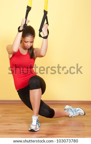 Stock Photo Beautiful young girl exercising in the gym with suspension device.
