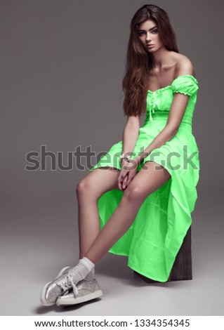 Beautiful young girl fashion girl in green dress on grey background
