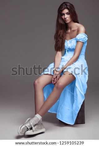 Beautiful young girl fashion girl in light blue dress on grey background