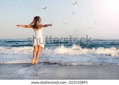 Beautiful young girl flying with seagulls on the sea #222510895