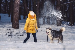 Beautiful young girl funny playing with her dog in winter in park. Woman funny throws snow at the dog. Happy winter holiday concept