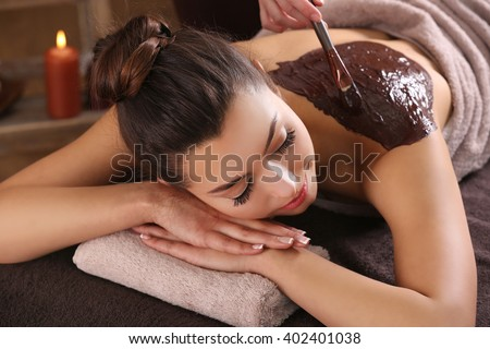 Beautiful young girl having cosmetic mask in spa salon
