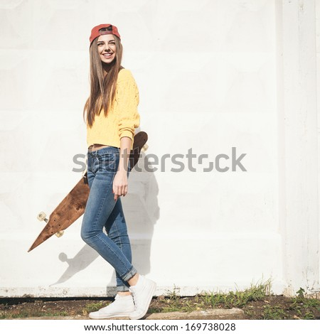 Beautiful young girl hipster walking with longboard in the afternoon Skateboarding Outdoors lifestyle