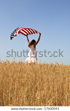 Beautiful young girl holding an American flag in the wind in a field of rye. Summer landscape against the blue sky. Vertical orientation.
