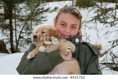 beautiful young girl holding golden retriever puppy