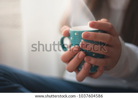 Beautiful young Girl holding her Cup of Coffee and Hot Chocolate-Indoor Atmosphere #1037604586