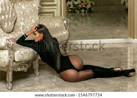 Beautiful young girl in a black bodysuit and boots in the living room. Attractive brunette model with long legs sits on the floor near the sofa and poses. Successful life theme. Horizontal photo. #1546797734