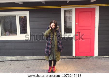 Beautiful young girl in a green jacket against the background of her own home.