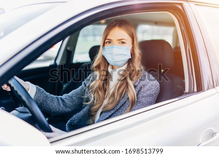 Beautiful young girl in a mask sitting in a car, protective mask against coronavirus, driver on a city street during a coronavirus outbreak, covid-19
