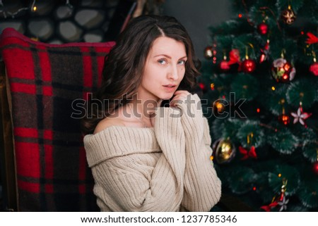 Beautiful young girl in a New Year's interior. A woman is sitting near the fireplace in a rocking chair. New Year. Christmas mood #1237785346