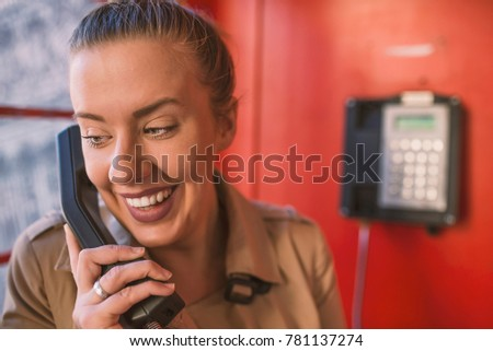 Beautiful young girl in a phone booth. The girl is talking on the phone from the payphone. English telephone booth in the street and a woman talking on the phone. Cheerful girl visiting London #781137274