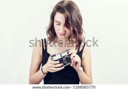 beautiful young girl in a short black dress takes pictures with an old vintage camera, a smile, a beautiful face, a brunette.