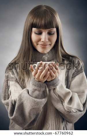 beautiful young girl in a sweater with a cup of hot beverage