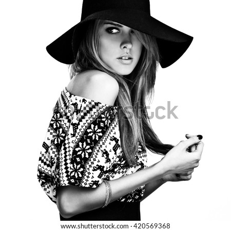 Beautiful young girl in a sweater with deer print and black hat. Black-white photo.
