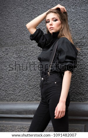 Beautiful young girl in black clothes with suspenders on a black wall background. Without filters. Natural color. #1091482007