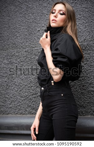 Beautiful young girl in black clothes with suspenders on a black wall background. Without filters. Natural color. #1095190592