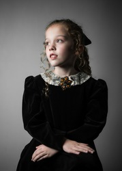 Beautiful young girl in black 1890s English Victorian 18th century child period dress with elegant white lace collar antique broach jewelery and long curly pretty hair looking away from camera