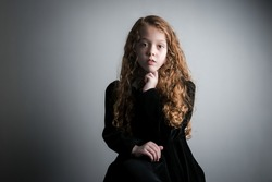 Beautiful young girl in black 1890s English Victorian 18th century child period dress with elegant white lace collar antique broach jewelery and long curly pretty hair looking at camera