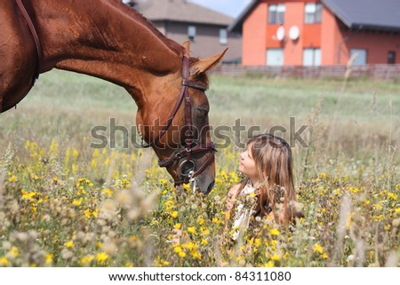 Beautiful young girl in brown dress sitting on the field with flowers and chestnut horse standing near