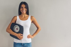 Beautiful young girl in casual wear is holding a weigh scales, looking at camera and smiling, on gray background