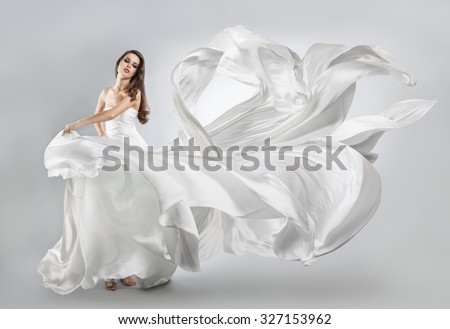 beautiful young girl in flying white dress. Flowing fabric