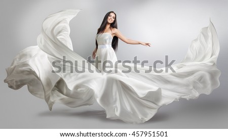 beautiful young girl in flying white dress. Flowing fabric. Light white cloth flying in the wind #457951501