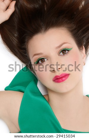 Beautiful young girl in green dress with fresh sexy makeup lying in white background