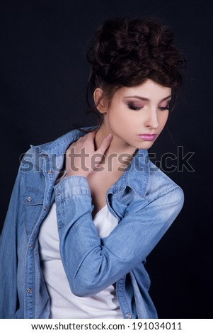 Beautiful young girl in jeans coat looking down, touching her neck. Black background.