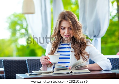 beautiful young girl in outdoor cafe reading a book and drinking coffee. phone. student. business woman
