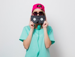 Beautiful young girl in pink cap and blue t-shirt with VHS cassette on white background.