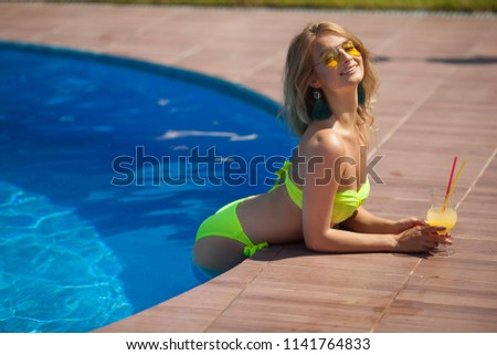beautiful young girl in sunglasses in summer pool with juice in hand #1141764833