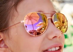 Beautiful young girl in sunglasses with beach umbrella reflection. Holidays, travel, vacation and happiness concept.