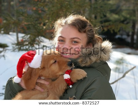 beautiful young girl in winter jacket holding adorable golden retriever puppy