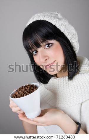 Beautiful young girl is holding a big white cup with coffee grains - stock photo