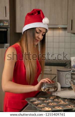 beautiful young girl is preparing Christmas muffins