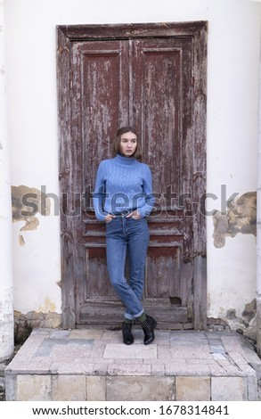 Beautiful young girl is standing on the stair in the blue jeans and blue sweater near old brown door. Street photo session. Street fashion.