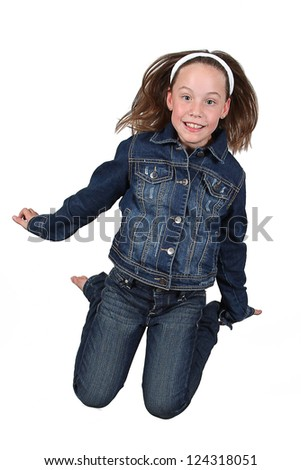 Beautiful young girl jumping in air on white background