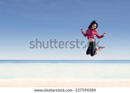 Beautiful young girl jumping the beach
