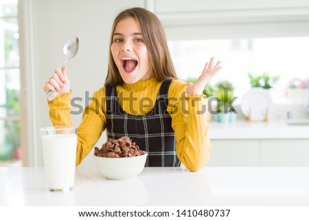 Beautiful young girl kid eating chocolate cereals and glass of milk for breakfast very happy and excited, winner expression celebrating victory screaming with big smile and raised hands