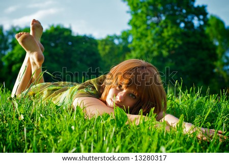 Beautiful young girl laying in grass