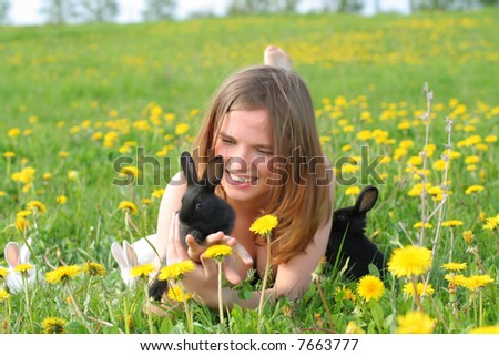 Beautiful young girl lays in grass and plays with cute small rabbits