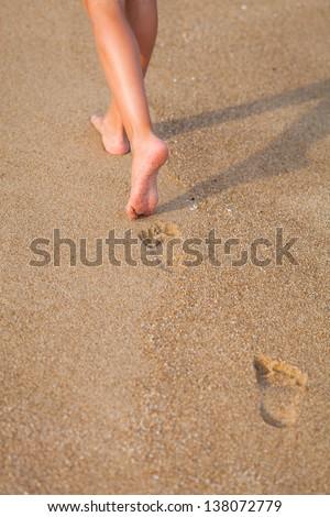 Beautiful young girl  legs, walking on the beach